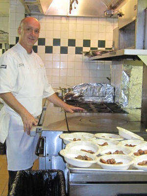 Sous Chef Leonard Reese shows off the French Plaque stoves in the Aquarelle kitchen.
