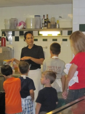 Aquarelle owner Terry Wilson gives children a tour of the kitchen before teaching them how to cook at a birthday party.